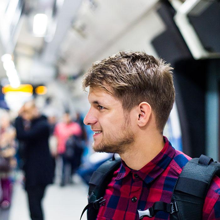чоловік з рюкзаком у метро дивиться на вагон